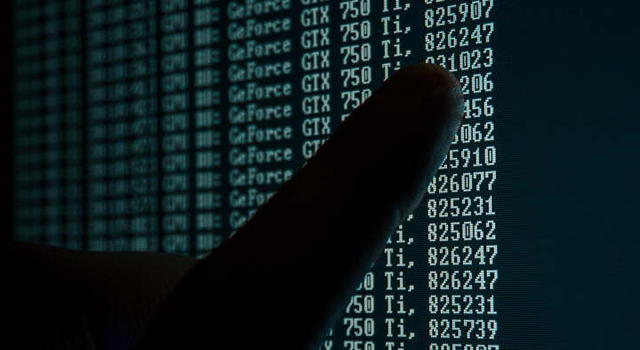 Platzhalterbild für 10 Fragen zum Datenschutz. Ein Finger auf einem dunklen Bildschirm mit kryptischen Zahlenreihen wie bei dem Film Matrix.