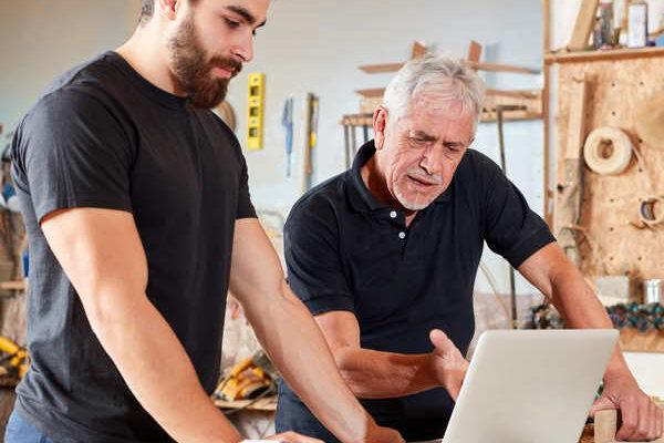 Ein Schreiner und sein Mitarbeiter schauen in der Werkstatt auf einen Laptop. Datenschutzfür alle Branchen, besonders für das Handwerk.