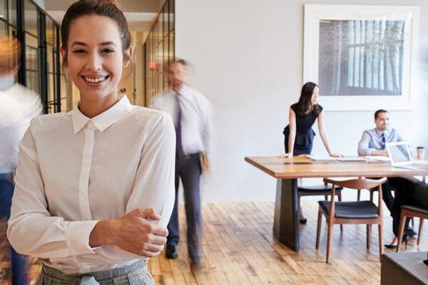 Eine junge Frau in einem sehr modernen Büro. Hinter ihr befinden Kollegen, die am arbeiten sind.
