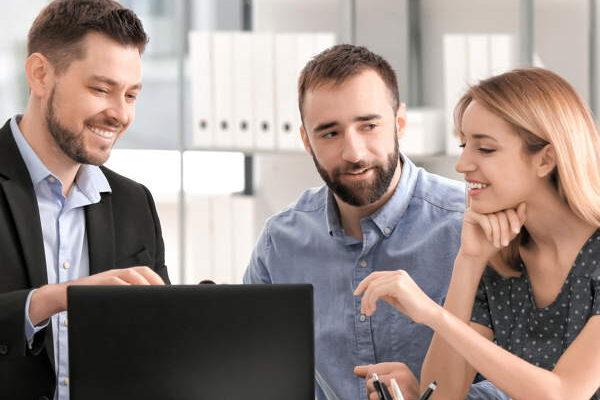 Eine junge Frau und ein junger mann sprechen mit ihrem Steuerberater, der vor einem geöffneten Laptop sitzt. Branchen wie Steuerberater und Wirtschaftsprüfer benötigen einen sicheren Datenschutz.